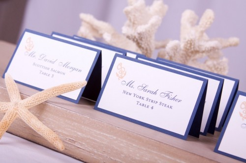 a wooden tray with navy and white escort cards and starfish is a cool idea to rock at a nautical or beach wedding
