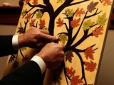 a painted tree and colorful leaves attached to it is a cute and casual idea for a fall wedding