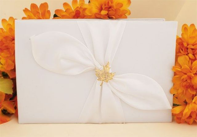 an elegant white wedding guest book accented with leaf drapery and a a gold leaf on top is refined