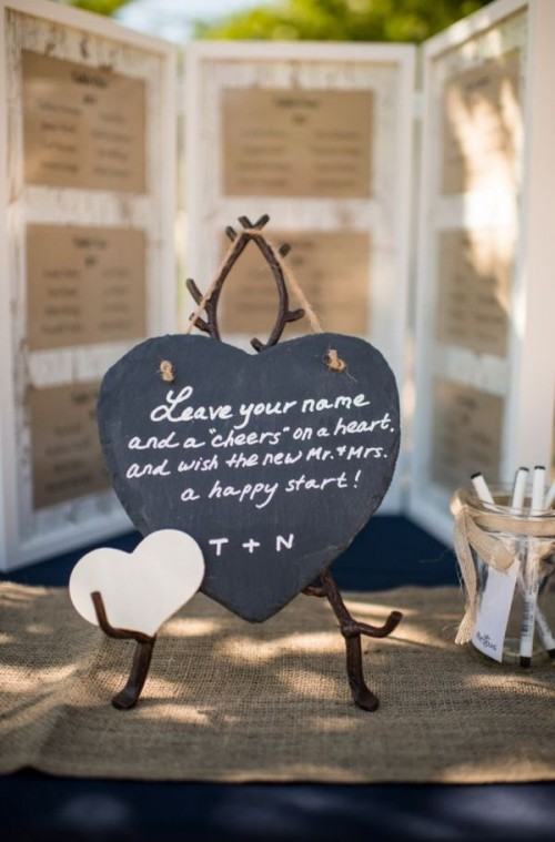 a chalkboard head stand with little paper hearts, on which the guests can leave messages