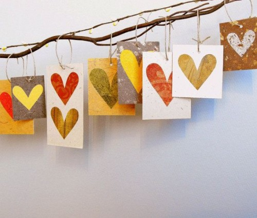 a branch with colorful hearts on paper pieces is a chic and fun idea of a fall wedding guest book