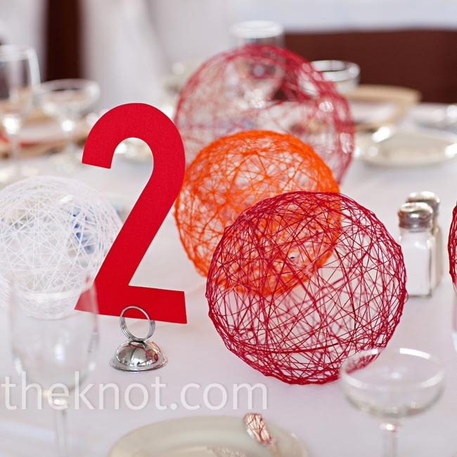 red and orange yarn spheres and a table number can be easily DIYed