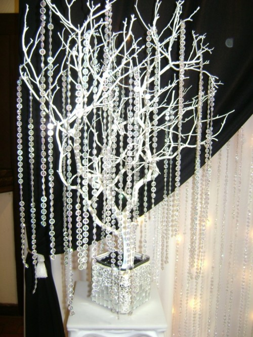 white branches in an embellished jar and long hanging crystal strands for a glam feel