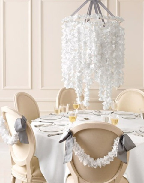 an overhead white faux blooms centerpiece will save the table space, and matching garlands on the chairs will help