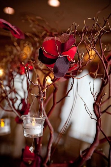 red branches with hanging candle lanterns and red fake blooms on them