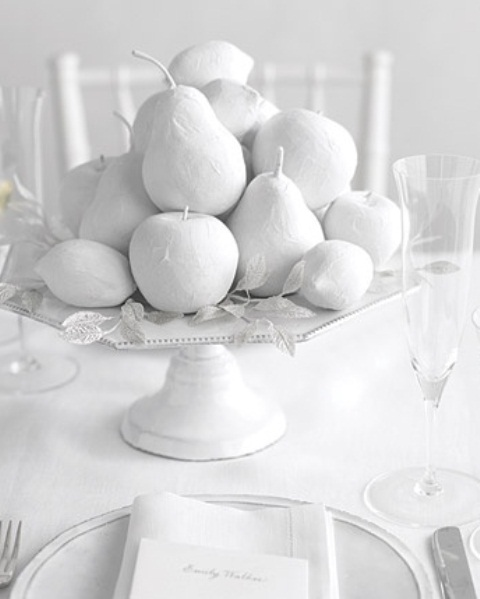 a white bowl with white paper mache fruits is an elegant vintage inspired centerpiece