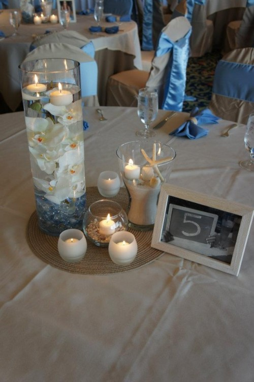 a jute rug, candles in candle holders, a vvase with blue crystals, white orchids and a vase with sand and starfish