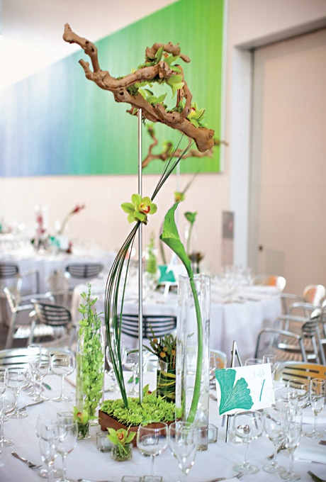 greenery, driftwood, green orchids on a stand for a chic and bright wedding centerpiece