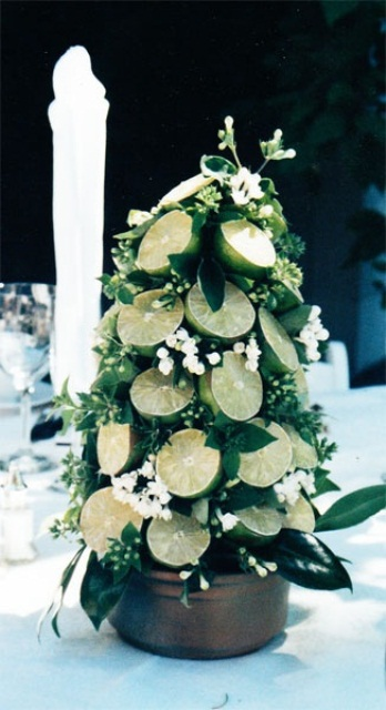 a greenery and lime wedding centerpiece shaped as a Christmas tree