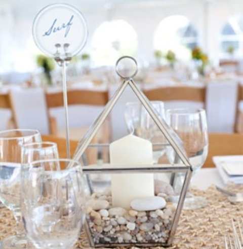 a metallic lantern with sand and pebbles and a large candle for a beach wedding