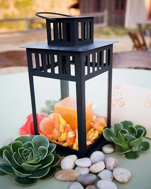 a black lantern with an orange candle, petals and succulents around for a summer or fall wedding