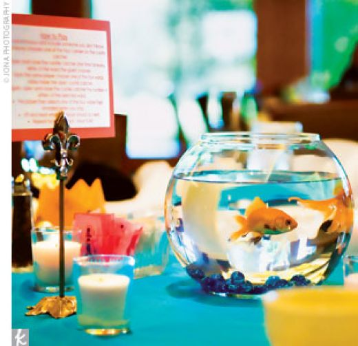 an aquarium with gold fish and blue pebbles is a cool idea with a living feel