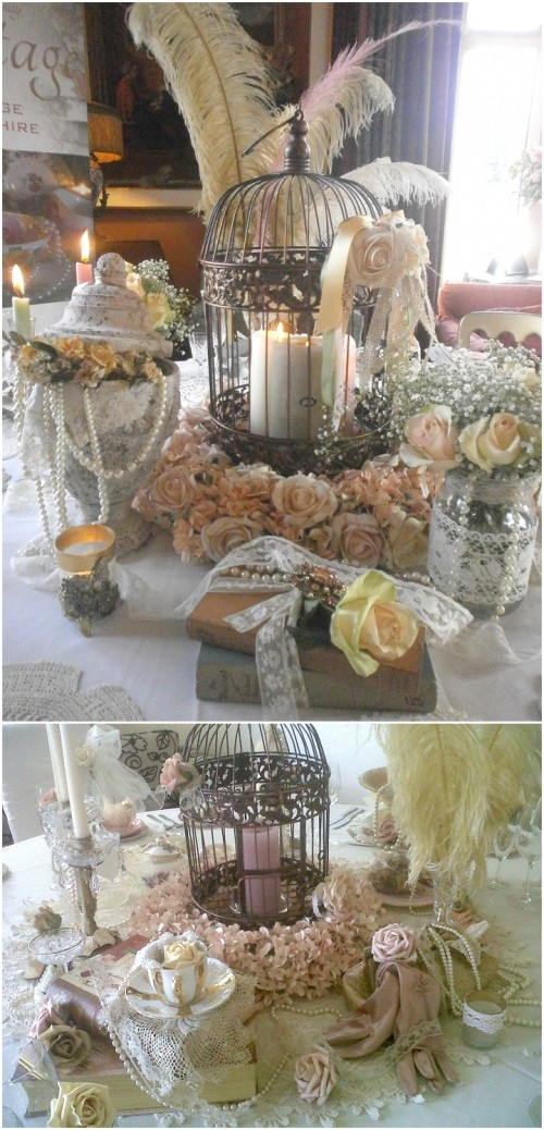 a vintage cage with pilalr candles, feathers, pearl strands and fake blooms for a vintage-inspired wedding