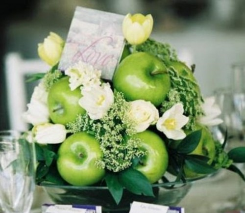 a green apple topiary with greenery, white blooms and a card on top for a bright wedding