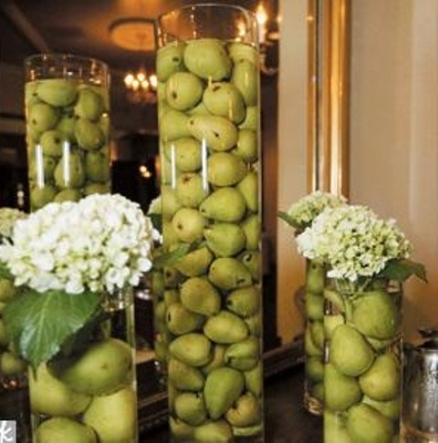 tall glass vases with green apples and pears floating inside them is a creative idea