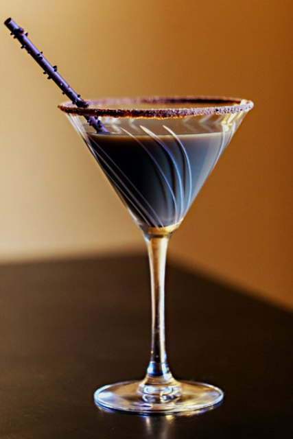 a chocolate cocktail with a chocolate edge and some confetti is a delicious signature drink type