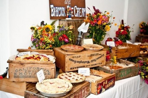 a stylish rustic fall wedding bar with homemade fruit pies served on crates and bright fall flowers for decor