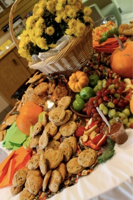 a rustic fall grazing table with grapes, apples, pumpkins, bakery and olive plus sauces