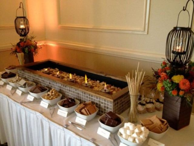 an s'more bar decorated with fall blooms and candle lanterns is a cool idea for fall and winter weddings