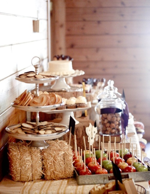 a rustic sweets bar with a stand with cookies on hay, a metal tray with candied apples, jars with macarons and a wedding cake