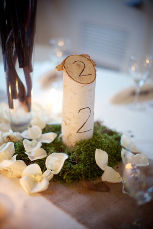 moss, petals and a tree branch cut with a wood burnt number is a nice idea for a fall rustic or woodland wedding