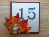 a framed table number, bright fall leaves and a piece of a branch will match a rustic or woodland fall tablescape