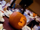 a jack-o-lantern with a carved table number and a candle inside is perfect for both fall and Halloween weddings