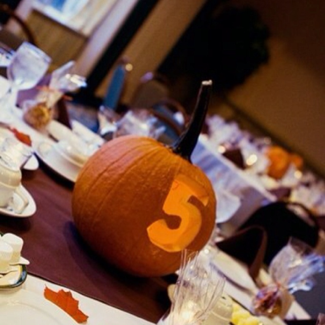 a jack o lantern with a carved table number and a candle inside is perfect for both fall and Halloween weddings