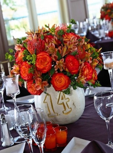 a white pumpkin with a painted table number and bright blooms and leaves is a stylish fall centerpiece
