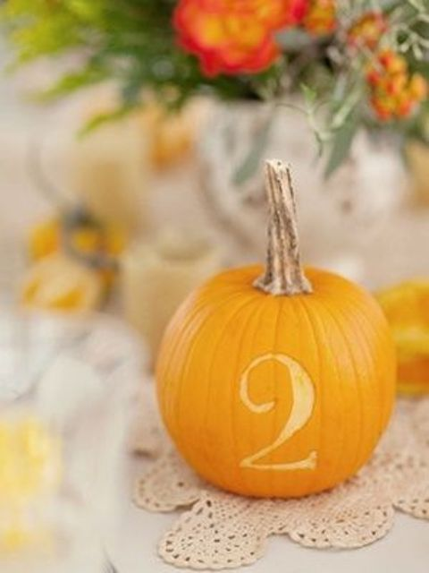 a pumpkin with a carved number placed on a doily is a lovely idea for a fall wedding