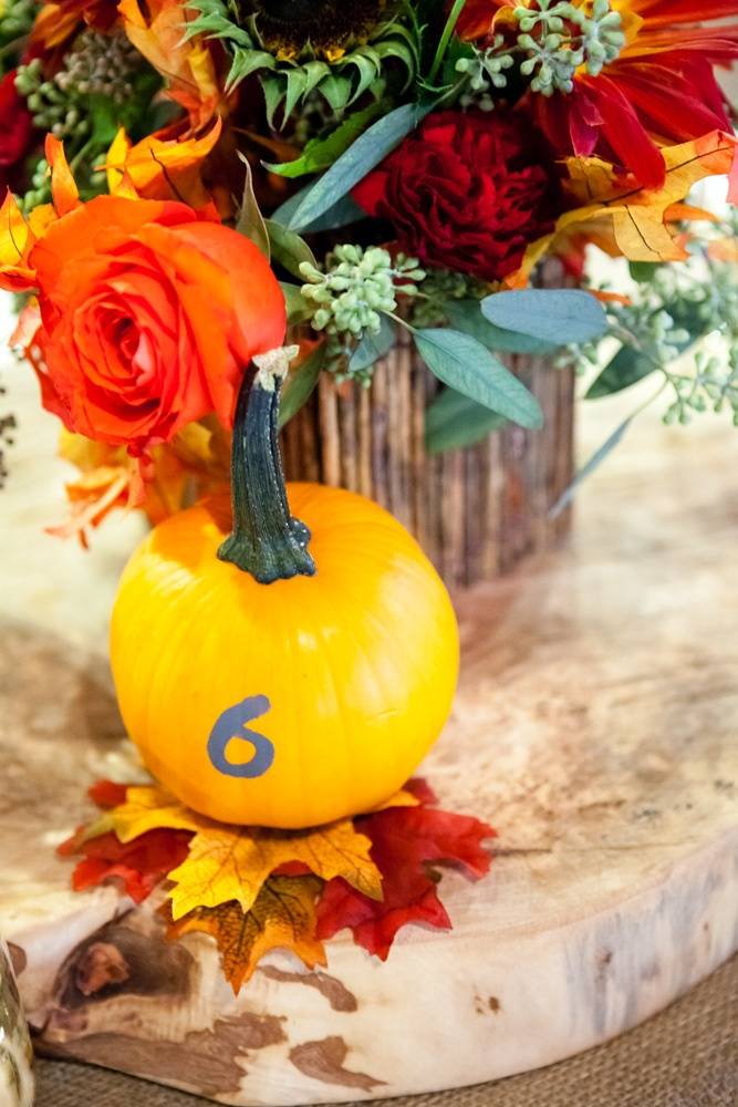 a pumpkin with a table number is always a good addition to a fall centerpiece, especially for a rustic one