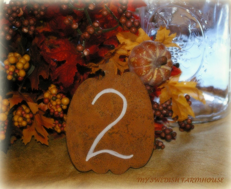 an orange plywood pumpkin with a table number is a nice decoration for a fall tablescape
