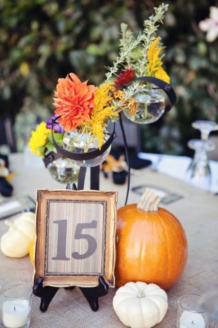 pumpkins, candles, a framed table number and bright flowers in creative sphere vases for a fall centerpiece