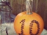 a pumpkin with cloves that form a table number is a very stylish fall centerpiece idea – just add some blooms