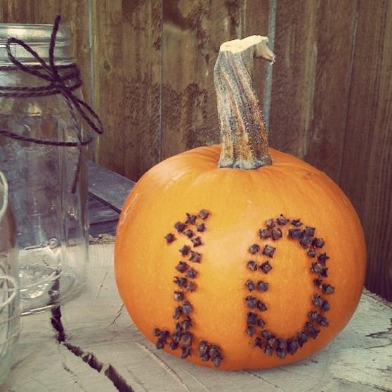 a pumpkin with cloves that form a table number is a very stylish fall centerpiece idea   just add some blooms