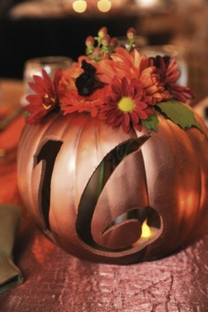a metallic rust-colored faux pumpkin with a cutout number, a candle inside and bright faux blooms on top
