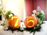bright pumpkins with cutout numbers and lights inside placed on fir branches and with blooms look very stylish