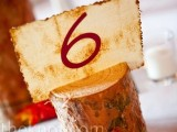 a tree stump with a printed table number is a nice bold decoration you may rock for your fall wedding