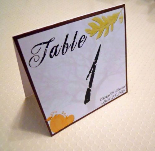 a printed table number with some leaves is a simple and cool item for a fall centerpiece