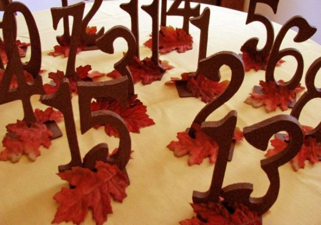 stained wooden table numbers with bright leaves are very bold and will fit a rustic fall tablescape