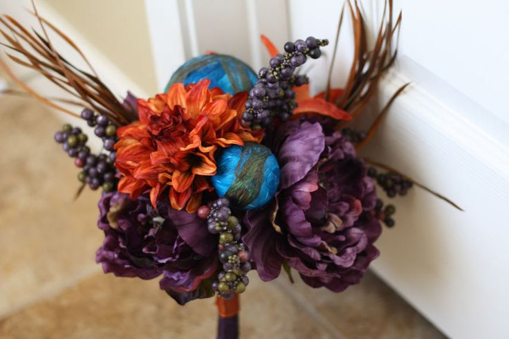 a creative Halloween wedding bouquet of purple and orange blooms, berries, dried grasses and blue spheres