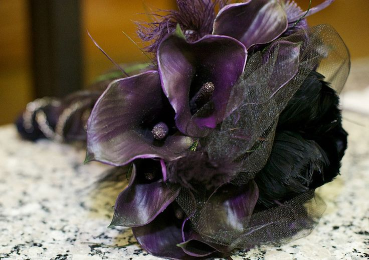 a dark Halloween wedding bouquet of deep purple callas, black and purple feathers, black tulle