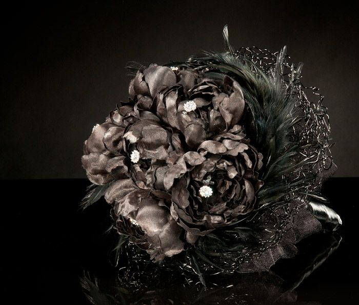 a black Halloween wedding bouquet of blooms, feathers, embellishments and with a dark tulle wrap