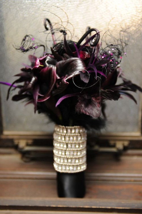 a sophisticated Halloween wedding bouquet of deep purple callas, feathers, lotus, twine with sequins and an embellished wrap