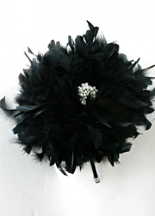 a glam black feather bouquet with an embellishment in the center is a refined and chic idea of a Halloween wedding bouquet
