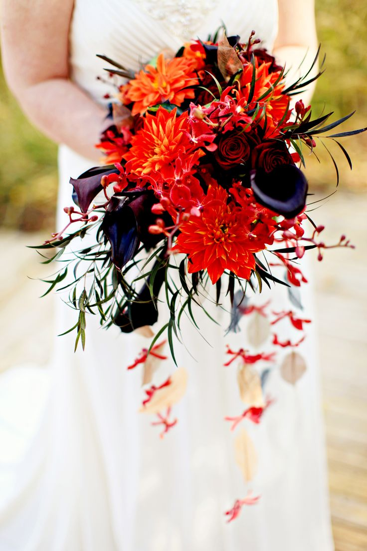 a bright Halloween wedding bouquet of red, orange and deep purple blooms, greenery and cascading red blooms