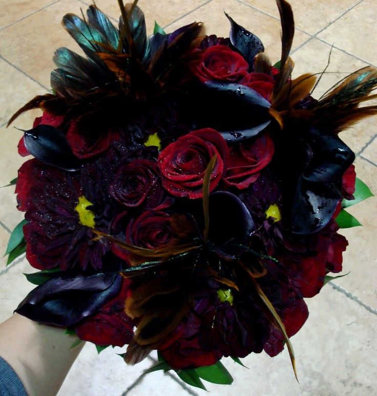a dark Halloween wedding bouquet of red, burgundy and black blooms, with feathers and shiny touches