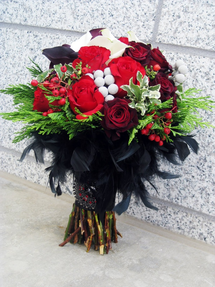 a bold Halloween wedding bouquet of red and burgundy blooms, lots of berries, greenery and black feathers