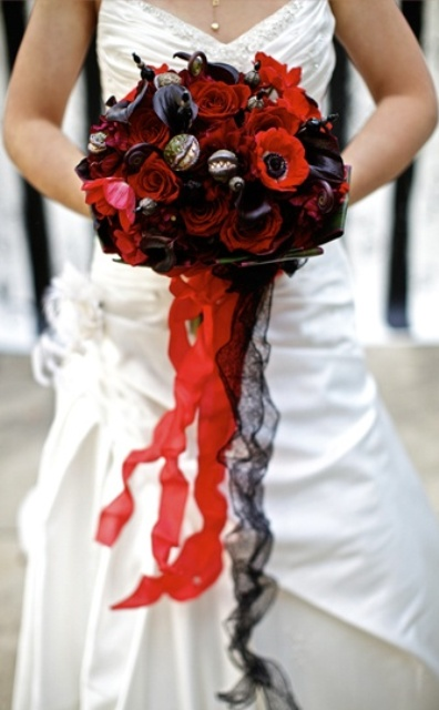 a catchy Halloween wedding bouquet of red, burgundy and dark blooms, berries and red and black ribbons for a Halloween wedding