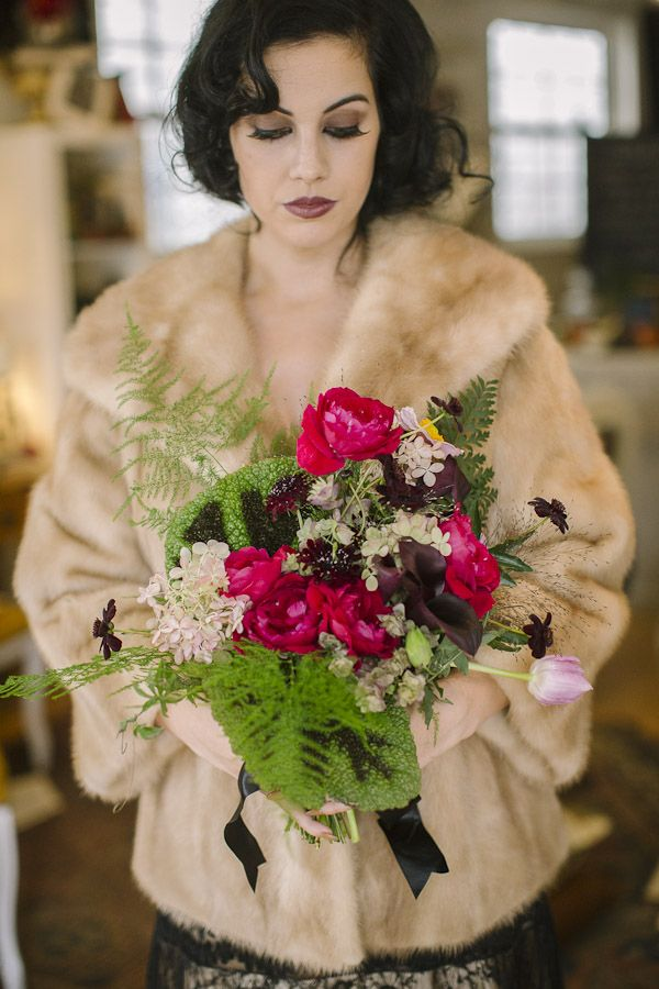 a statement wedding bouquet of hot pink blooms, white ones, dark callas, fern and foliage is very stylish